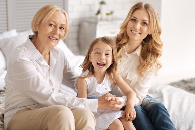 Bambina sveglia che scoppia a ridere mentre è seduta tra la sua affascinante madre e la nonna che si tengono per mano insieme intorno a lei