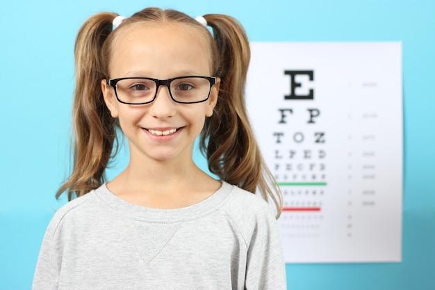 Bambina carina controlla la vista con un test della vista oftalmologo