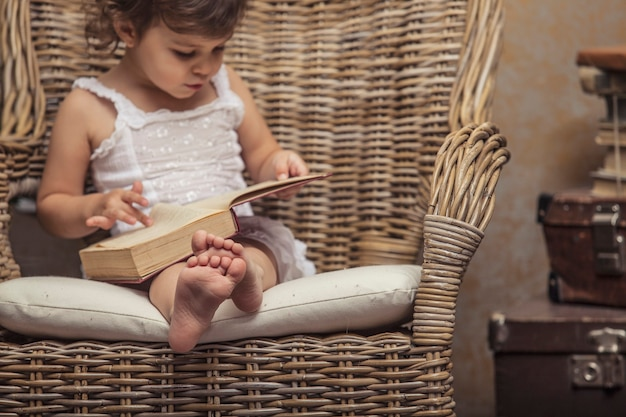 Bambina carina su una sedia, leggendo un libro in interni retrò