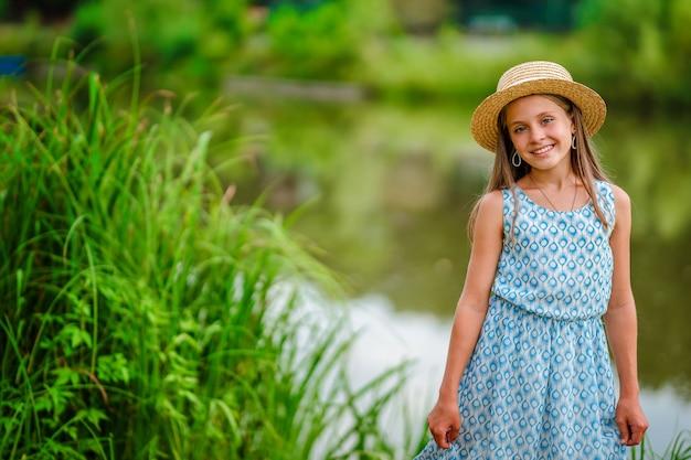 Bambina carina con un cappello e un vestito sulla riva di un lago favoloso