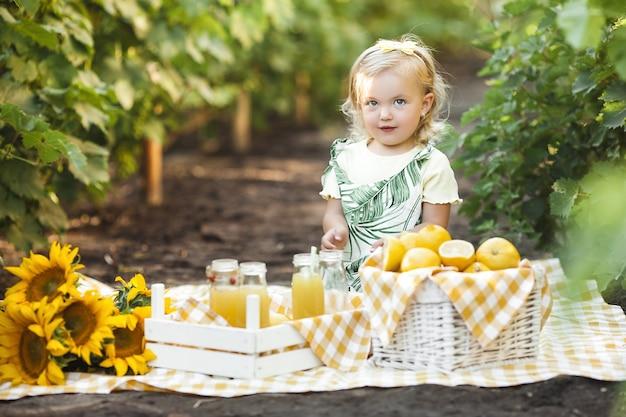Ritratto sveglio del primo piano della bambina sulla priorità bassa di estate.