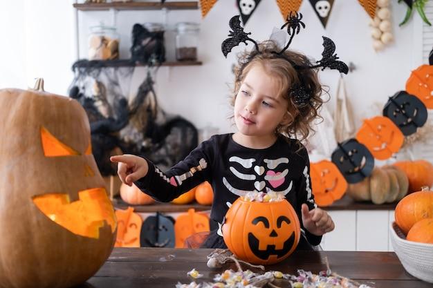Carina bambina in costume da strega che tiene in mano un jack zucca con caramelle che si diverte in cucina festeggia...