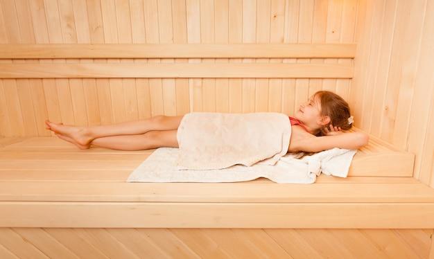 Bambina sveglia coperta di asciugamano sdraiata al bagno di vapore Foto Premium