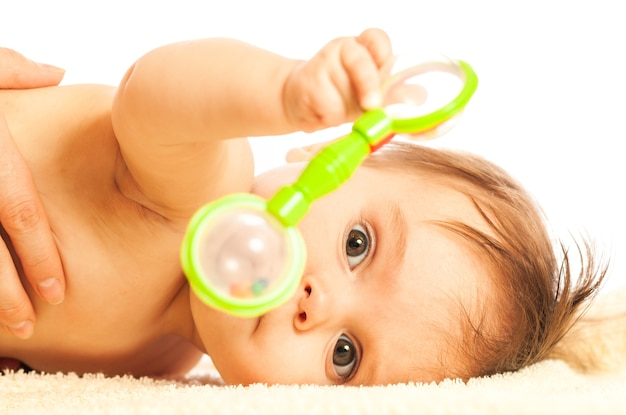 Bambina sveglia in un pannolino con un sonaglio nelle sue mani