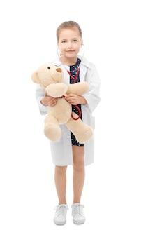 Bambina sveglia in uniforme del medico che gioca con l'orso del giocattolo su bianco