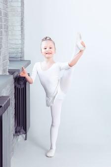 Una bambina carina sogna di diventare una ballerina bambina con un vestito da ballo bianco che balla
