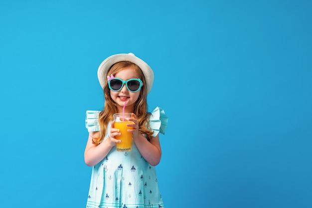 Ragazza carina in un abito, cappello e occhiali da sole pone