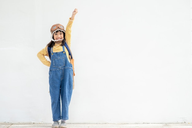 Una bambina carina vestita con un berretto e occhiali da pilota. il bambino sogna di diventare un pilota.