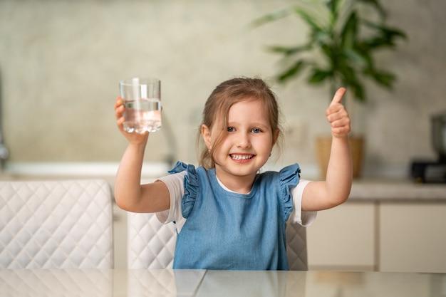 Acqua potabile della bambina sveglia in cucina a casa. prevenzione della disidratazione
