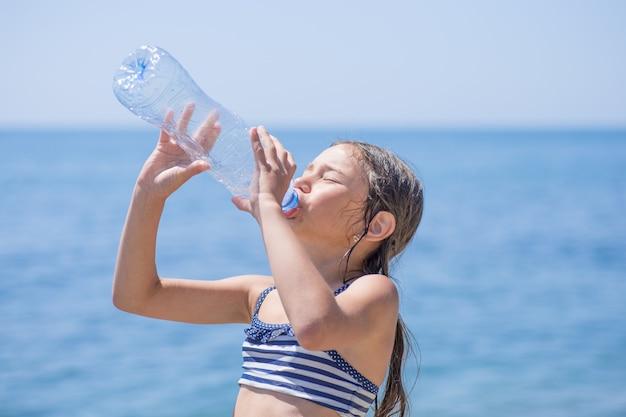 La bambina sveglia beve l'acqua dalla bottiglia vicino al mare. assistenza sanitaria, concetto di stile di vita.