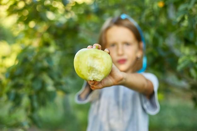 La bambina sveglia mangia la mela verde nel giardino domestico all'aperto, bambino felice, fa i fronti, raccolto autunnale, melo, stile di vita alimentare vegetariano di dieta sana di nutrizione.