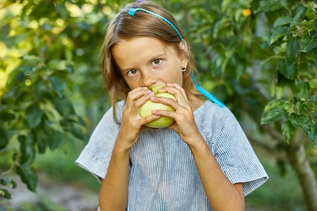 La bambina sveglia mangia la mela verde nel giardino domestico all'aperto, bambino felice
