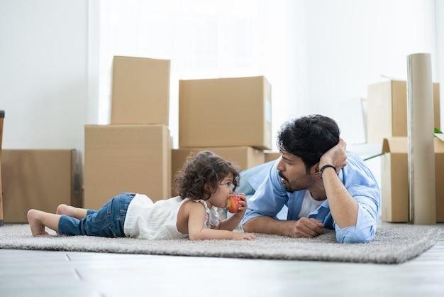 Bambina sveglia che mangia mela sdraiata con il padre si guarda mentre il padre si rilassa dopo aver imballato le scatole per spostare la nuova casa