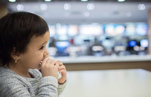 Bambina sveglia che mangia un hamburger nel fast food
