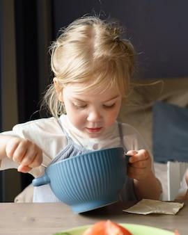 Bambina carina che mangia zuppa a pranzo mentre è seduta a tavola a casa