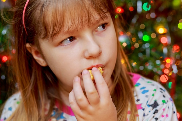 La bambina sveglia mangia la torta sakotis capodanno e buon natale sfondo