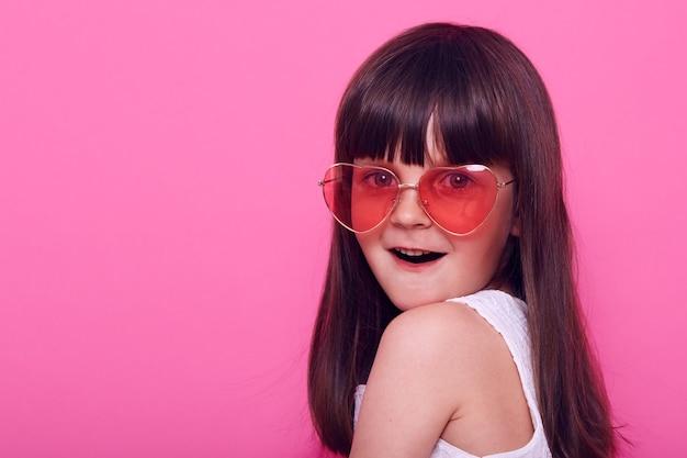 La bambina sveglia in vestito bianco elegante e occhiali a forma di cuore guarda davanti con la bocca aperta e l'espressione facciale stupita, vede cose incredibili, isolate sopra il muro rosa
