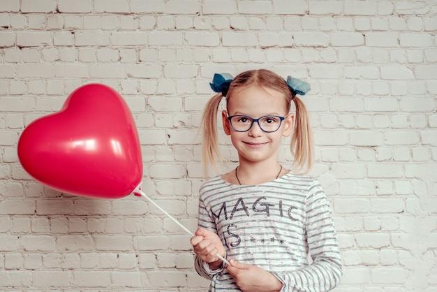 Bambina sveglia in occhiali con palloncino a forma di cuore rosso su sfondo bianco muro di mattoni, sfondo di san valentino