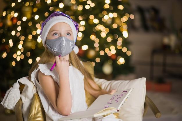Bambina sveglia in maschera facciale scrivendo lettera a babbo natale vicino all'albero di natale