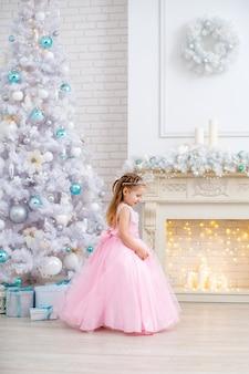 Bambina sveglia in vestito operato e diadema con l'albero di natale