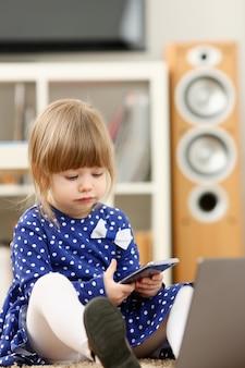 La bambina sveglia sul tappeto del pavimento usa il cellulare