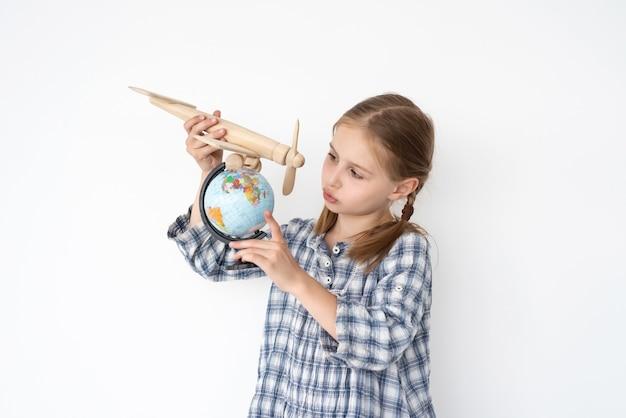 Bambina sveglia che vola aereo di legno sopra il globo sulla parete bianca