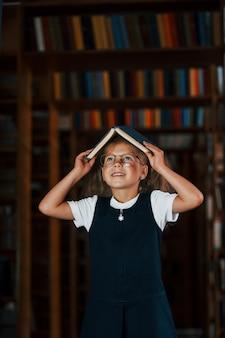 Una ragazzina carina con gli occhiali sta in biblioteca piena di libri