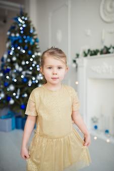 Bambina carina in abito color oro in posa sullo sfondo dell'albero di natale guarda la telecamera