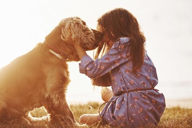La bambina carina fa una passeggiata con il suo cane all'aperto durante il giorno