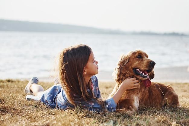 La bambina carina fa una passeggiata con il suo cane all'aperto in una giornata di sole