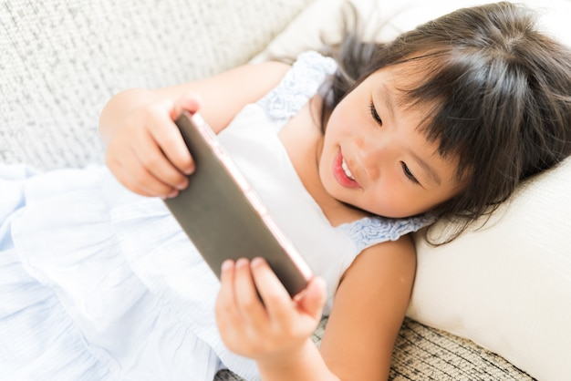 Bambina sveglia divertendosi per giocare sullo smart phone che si trova sul sofà