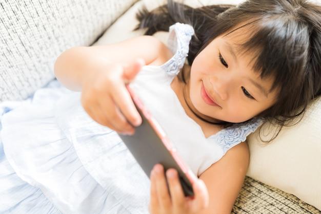 Bambina sveglia divertendosi da giocare sullo smart phone