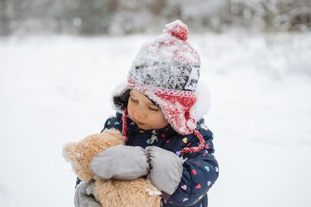 Bambina sveglia divertendosi a giocare all'aperto durante la nevicata. inverno nevoso.