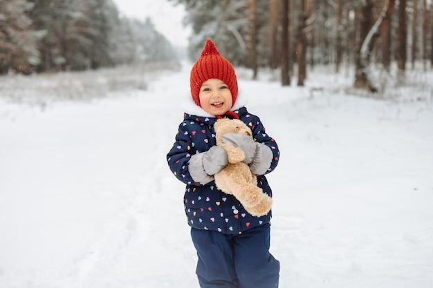 Bambina sveglia divertendosi a giocare fuori nella neve, tenendo l'orsacchiotto e indossando il cappello lavorato a maglia rosso brillante.