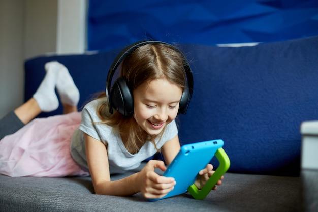 Bambina carina in cuffia sdraiata sul divano con un tablet digitale, kid addicted to technology