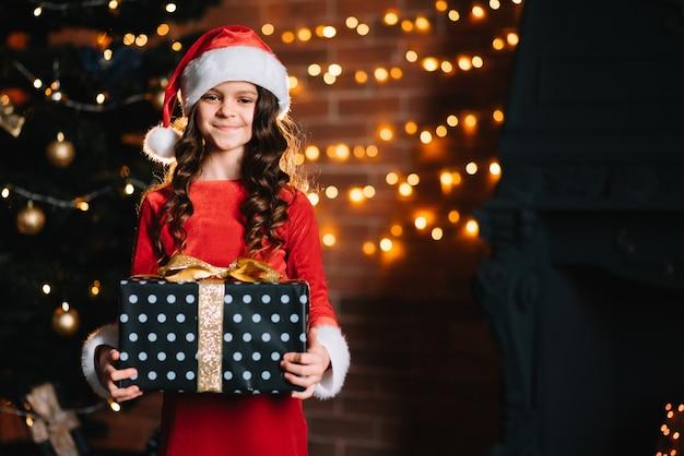 Bambina sveglia che tiene un regalo vicino all'albero di natale in un costume rosso della santa