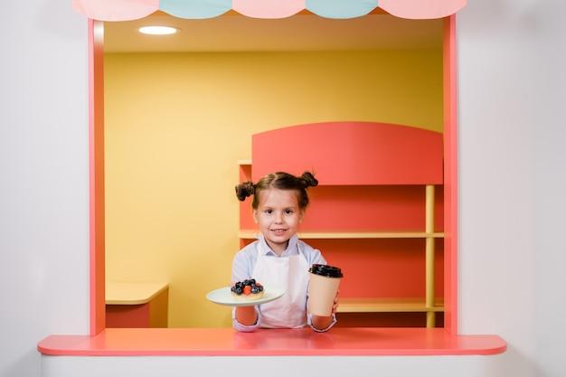 Bambina sveglia che tiene un bicchiere di bevanda e piatto con torta di bacche o dessert mentre lo passa agli ospiti della caffetteria