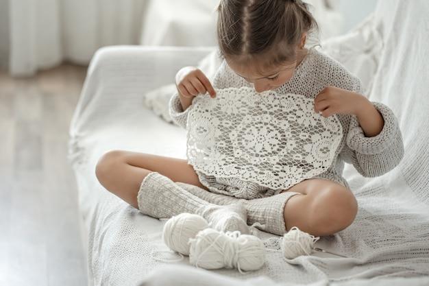 Bambina sveglia che tiene in mano un tovagliolo traforato fatto a mano.