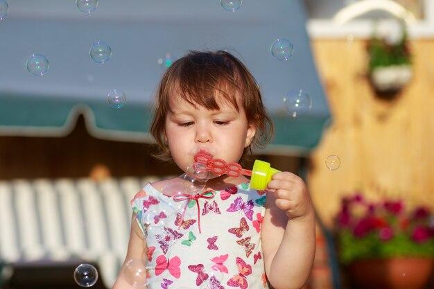 La bambina sveglia sta soffiando le bolle di sapone