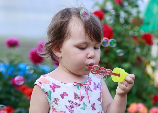 La bambina sveglia sta soffiando le bolle di sapone.
