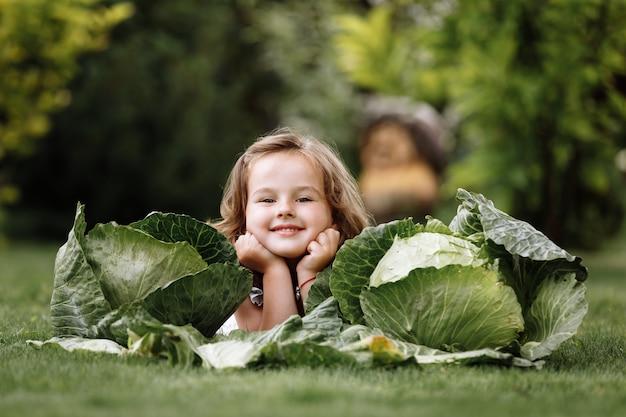 La bambina sveglia si diverte e si trova sull'erba verde vicino ai cavoli