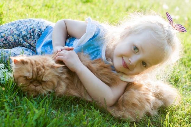 La bambina sveglia sta tenendo un gatto rosso in natura che si siede sull'erba
