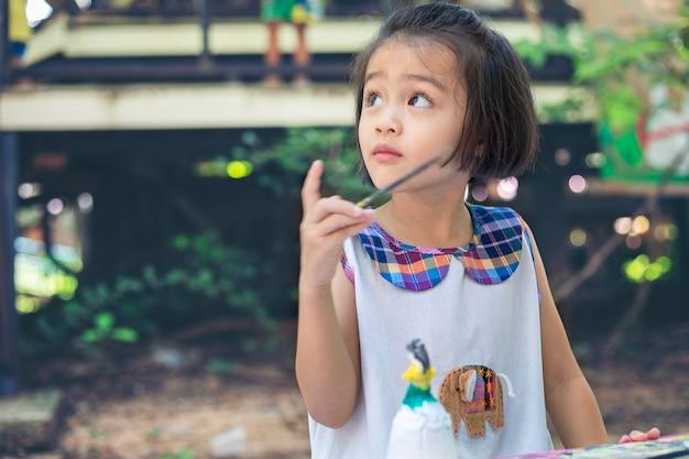 La bambina sveglia sta imparando fuori dall'aula felicemente con una natura meravigliosa e un sorriso luminoso
