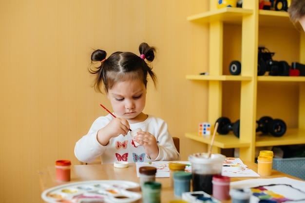 Una bambina carina sta giocando e dipingendo nella sua stanza. ricreazione e intrattenimento.