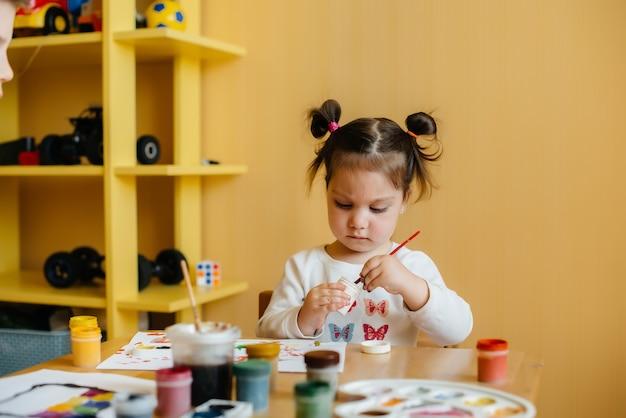 Una bambina carina sta giocando e dipingendo nella sua stanza