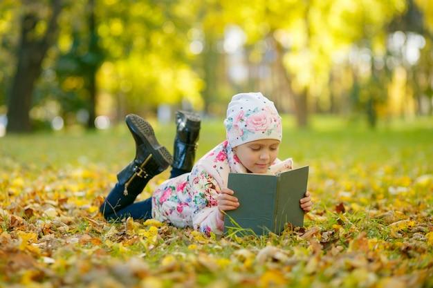 La bambina sveglia sta leggendo un libro mentre metteva sulle foglie di autunno gialle