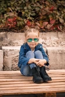 Una bambina carina è seduta con gli occhiali da sole su una recinzione di pietra. bambino alla moda in una giacca blu. stile casual, moda per bambini, abito alla moda, infanzia felice
