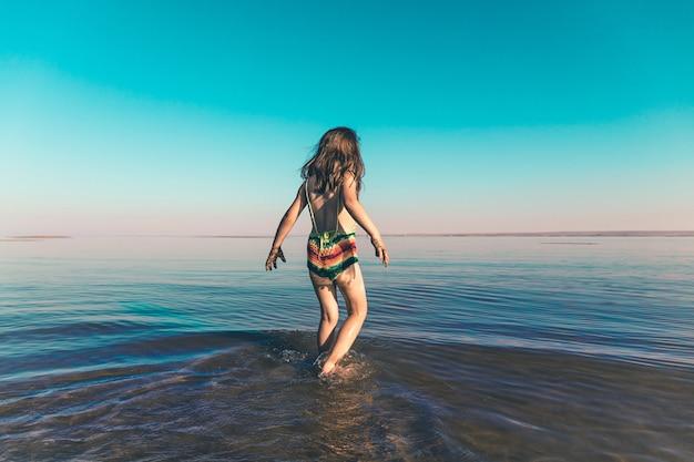 Una bambina carina in costume da bagno a maglia entra per la prima volta nella fredda acqua di mare nella stagione