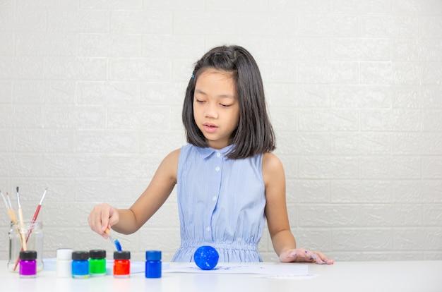 Bambina sveglia che impara con il colore della pittura sulla palla della schiuma