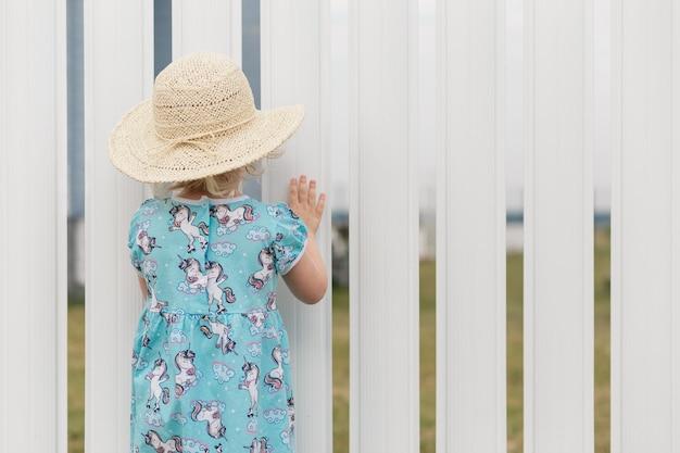 Bambina sveglia che guarda qualcosa attraverso il recinto